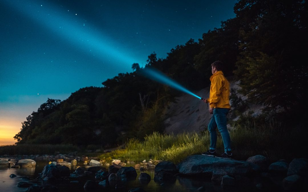 man shining flashlight into night sky